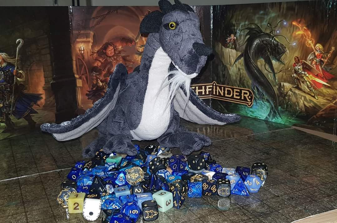 A picture of a toy dragon amongst a pile of Dungeon's and Dragons die.