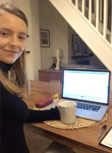 An image of Sarah Clayton working from home at her dining table