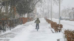 Photo of a snowy road with a child on a bicycle by Denise Jans
