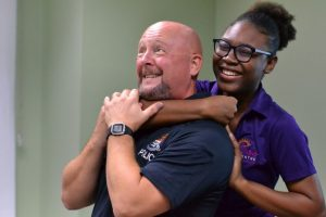 Police Training Officer PC James Fordyce and Renee Francis, a relief worker at the Cayman Islands Crisis Centre, demonstrate a hold during the personal safety awareness training.
