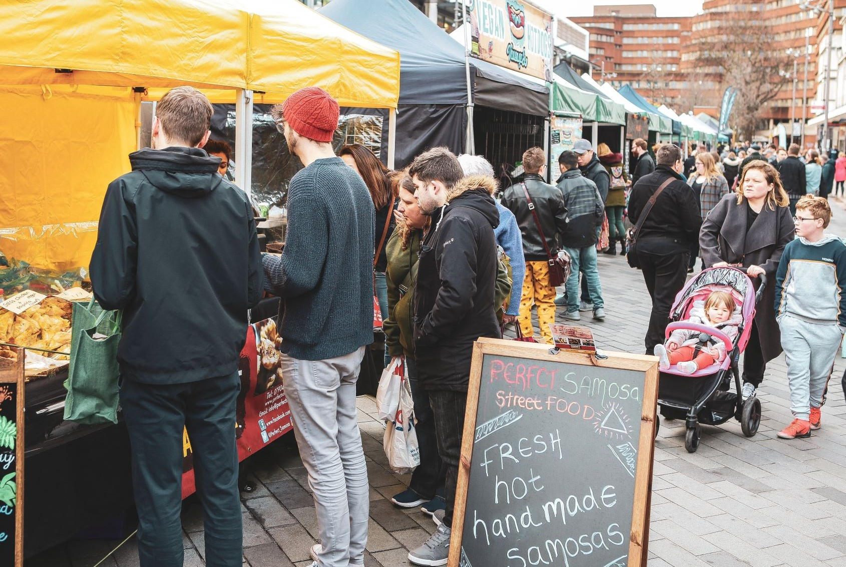 A crowd of people at the Sheffield Vegan Market. People are dressed for winter. There is a blackboard advertising samosas outside a stall.
