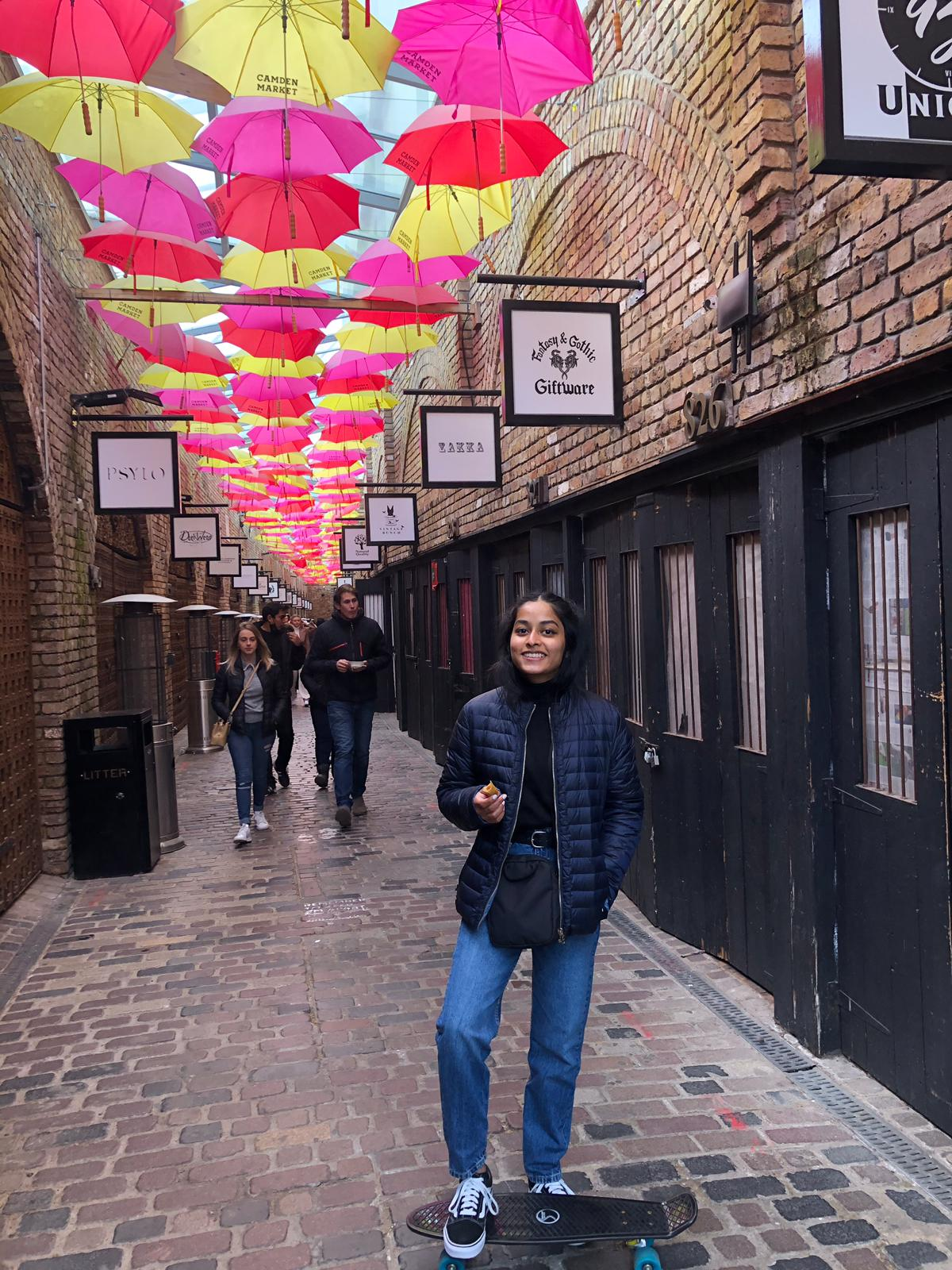 Savindri in an alleyway with an art installation of pink and yellow umbrellas hanging above. She is wearing blue jeans and a dark blue jacket. Her right leg is on a black skateboard